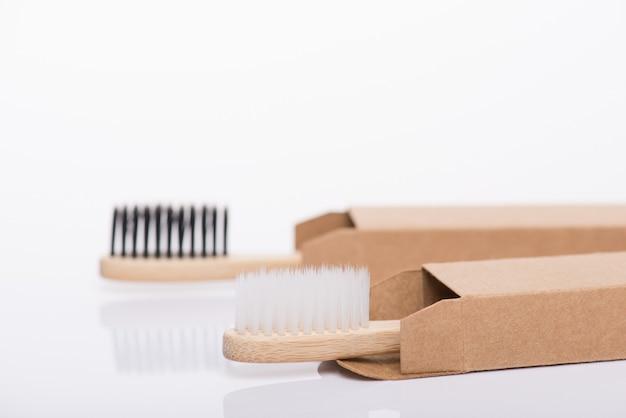 Close-up side profile view photo de eco-friendly emballé dans des brosses à dents en papier noir et blanc carton recyclé isolé sur fond blanc