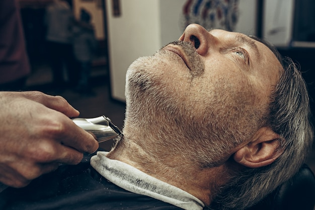 Close-up side profile view portrait of handsome senior barbu caucasian man getting beard grooming in modern barbershop.