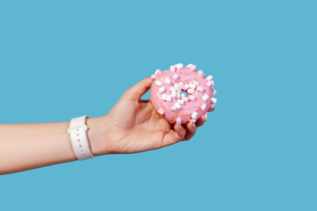 Close up side view female hand holding sweet donut rond avec glaçage rose,