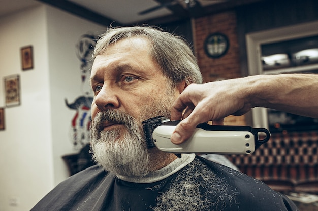 Close-up side view portrait of handsome senior barbu caucasian man getting beard grooming in modern barbershop.