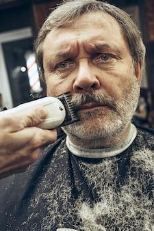 Close-up side view portrait of handsome senior barbu caucasian man getting beard grooming in modern barbershop.