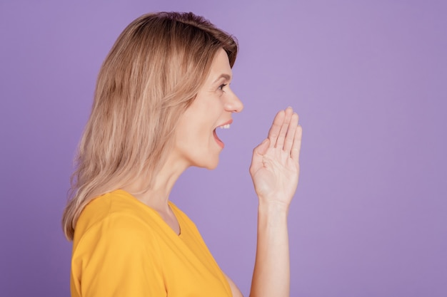 Close up side-view portrait of woman racontant des nouvelles en criant et tenant la main près de sa bouche ouverte isolée sur fond violet