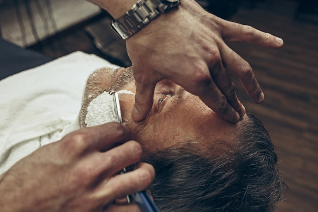 Close-up side vue de dessus beau senior barbu caucasien homme se barbe dans un salon de coiffure moderne.