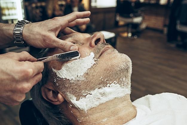 Close-up side vue de dessus beau senior barbu caucasien homme se barbe toilettage dans un salon de coiffure moderne.