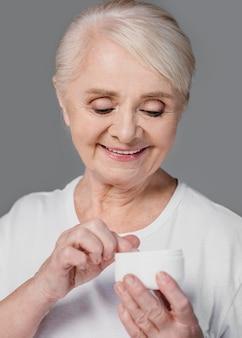 Close-up smiley femme tenant un récipient de crème