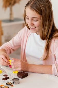 Close-up smiley fille jouant avec de l'argile