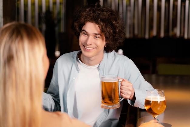 Close-up smiley homme et femme au pub