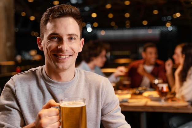 Close-up smiley homme tenant une chope de bière