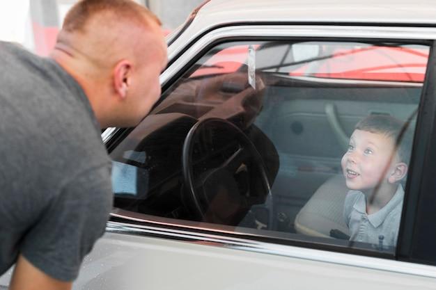 Close-up smiley kid assis dans la voiture