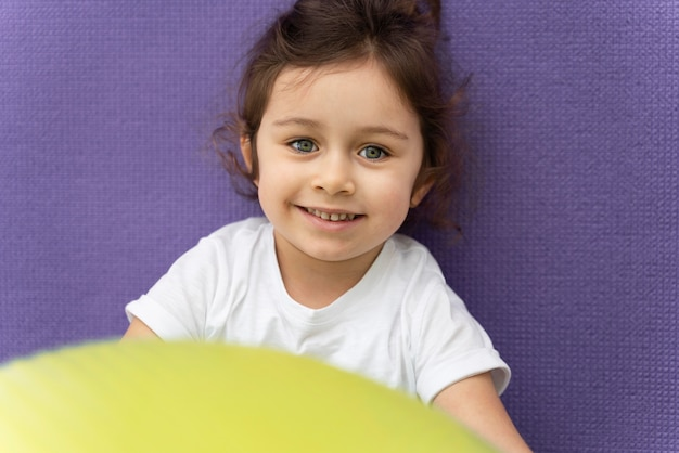 Close-up smiley kid holding gym ball