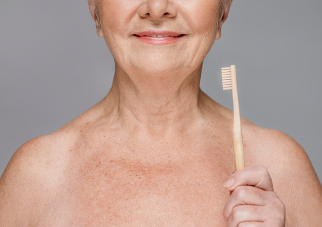 Close-up smiley woman holding brosse à dents