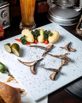 Close up de sprat épicé poêlé aux concombres marinés et pommes de terre bouillies sur fond blanc