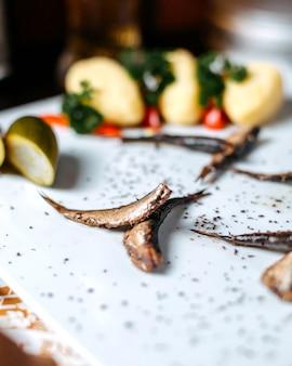 Close up de sprat épicé poêlé avec des concombres marinés sur fond blanc