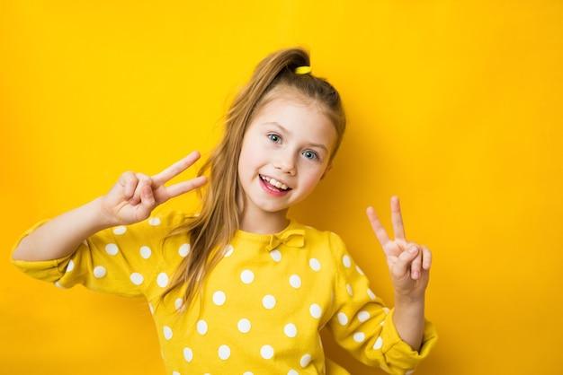 Close up studio photo portrait de douce belle intelligente avec sourire rayonnant fille de l'école faisant donnant v-sign isolé fond jaune vif