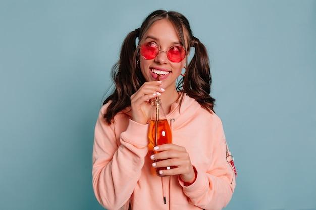 Close up studio portrait of dreamy belle fille avec des cheveux recueillis portant des lunettes rondes roses et pull rose boire du jus sur mur bleu isolé