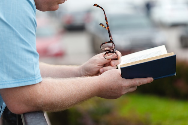 Close up study man lit un livre sur le gazon sous l'ombre des arbres avec la lumière du soleil dans le parc