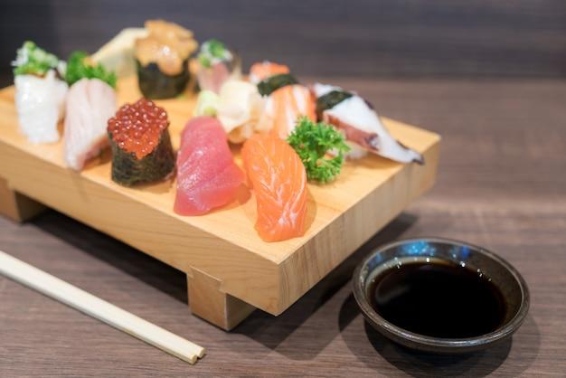 Close-up sushi et sashimi mélangés sur une plaque en bois sur une table en bois noire. nourriture japonaise.