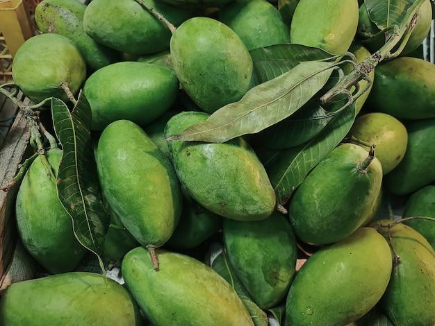 Close-up tas de mangues vertes fraîches avec des feuilles