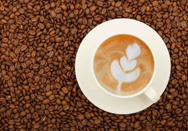 Close up tasse blanche sur soucoupe pleine de café latte cappuccino sur les grains de café torréfiés, vue de dessus, directement au-dessus
