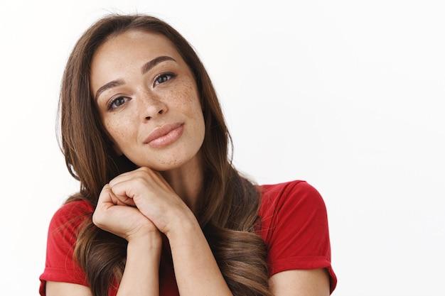 Close-up tendre, féminine jolie femme brune avec des taches de rousseur, s'appuyer sur l'épaule et soupirant de manière romantique, serrer les mains ensemble posant sensuellement et coquet, souriant mur blanc heureux