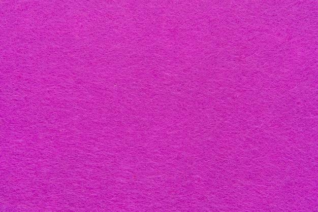 Close up de texture de tissu en feutre rose vif de tissu laineux rugueux de couleur rose un morceau rose intense de tissu en feutre texturé avec toucher rugueux