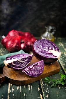 Close up tranché et demi de chou violet sur fond de bois vert dans un style rustique