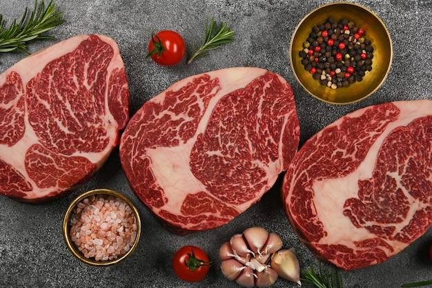 Close up trois steaks de bœuf ribeye crus marbrés aux épices, sur table en pierre, vue de dessus élevée, directement au-dessus