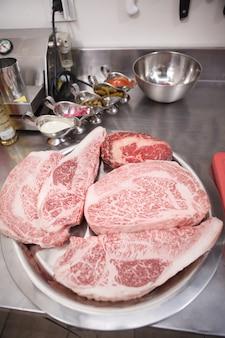 Close up vertical de steaks de boeuf marbrés crus frais sur une assiette