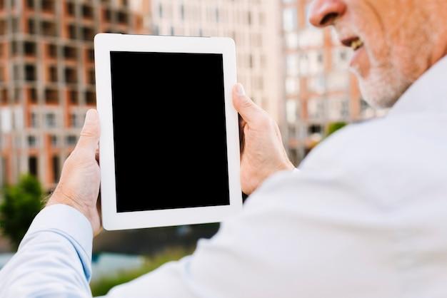 Close-up vieil homme brandissant une tablette