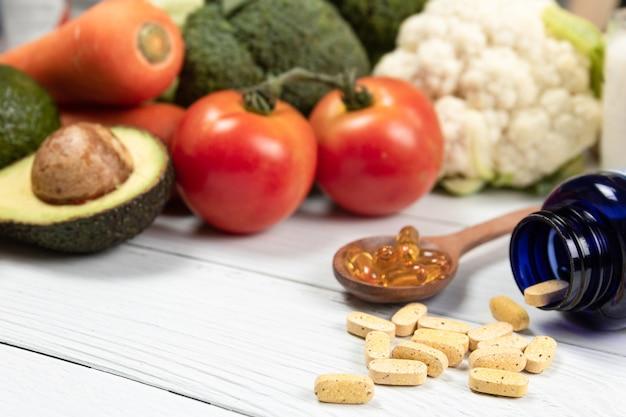 Close up vitamines et suppléments sur une table en bois blanc avec une bouteille bleue