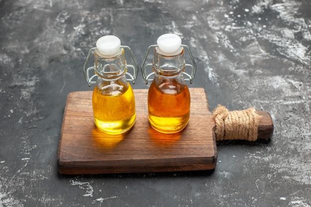 Close up vue aérienne de deux bouteilles d'huile sur une planche à découper