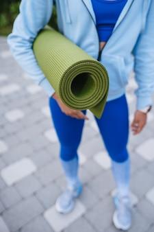 Close-up woman holding roll fitness ou tapis de yoga après avoir travaillé dans le parc.