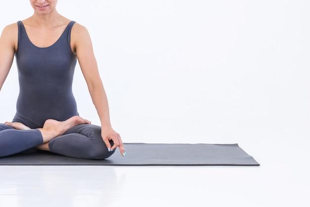 Close-up woman practicing yoga assis sur un tapis en position du lotus