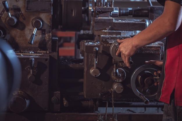 Close-up worker gère le métal au tour opérant la rectifieuse en uniforme avec sécurité