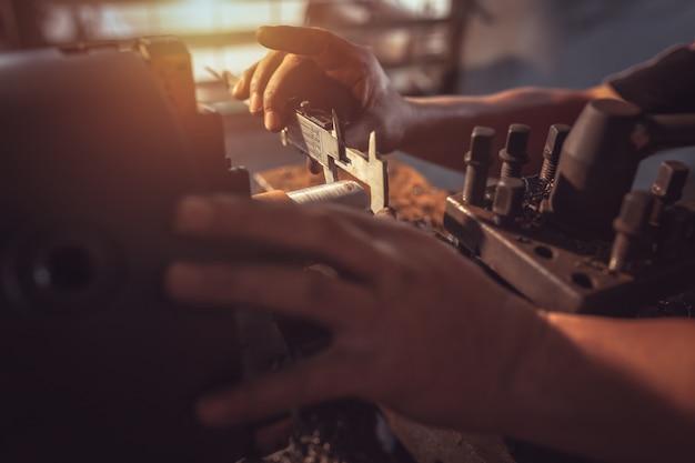 Close-up worker manipule du métal au tour turner mesure les dimensions de la pièce métallique avec un pied à coulisse en uniforme avec sécurité. travaillez sur un tour.