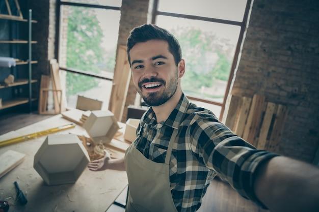 Close up workman professionnel réussi se sentir positif faire selfie tenir la main montrer son renouvellement de la production d'étagères en bois dur dans le garage de la maison