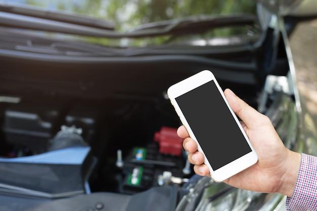 Close up young business man part à l'aide d'un téléphone intelligent mobile appeler un mécanicien automobile demander de l'aide parce que la voiture est cassée
