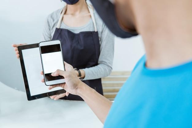 Close up young female shopkeeper servir client paiement en ligne de code à barres qr