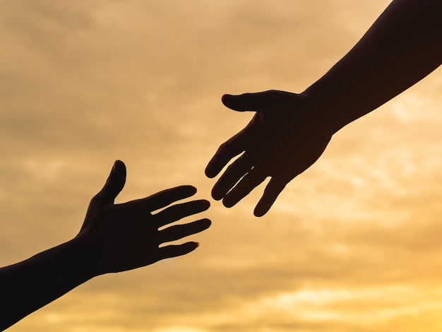 Closeup aider les mains sur le fond de ciel coucher de soleil