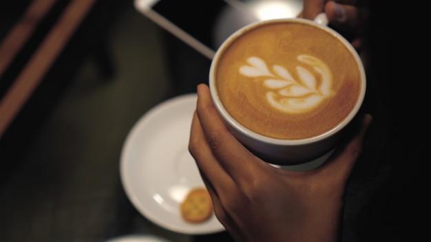 Closeup art latte sur le dessus dans des tasses à café de la main de femme tenant au café