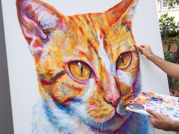 Closeup artiste peindre portrait gingembre chat sur toile blanche.