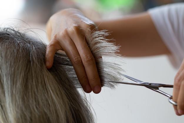 Closeup barbier avec des ciseaux coupe les cheveux