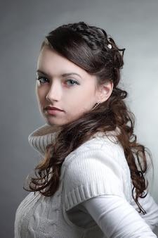 Closeup.belle jeune femme en pull blanc posant devant la caméra.