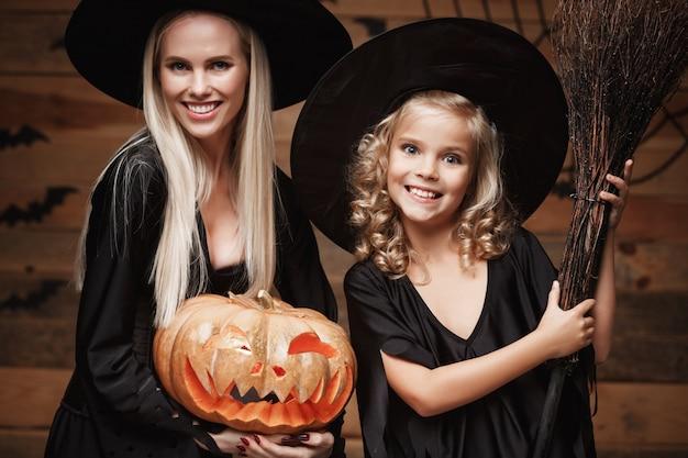 Closeup belle mère caucasienne et sa fille en costumes de sorcière célébrant halloween posant avec des citrouilles courbées