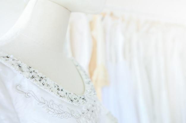 Closeup belle robe de mariée sur un modèle de cintres en magasin de robe de mariée