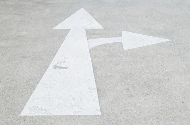 Closeup blanc peint flèche signe sur fond de plancher de rue de ciment