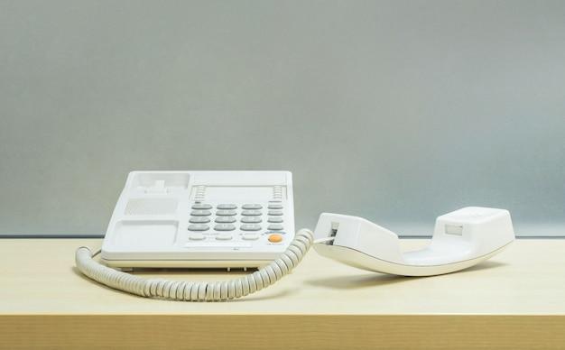 Closeup blanc téléphone, téléphone de bureau sur un bureau en bois flou