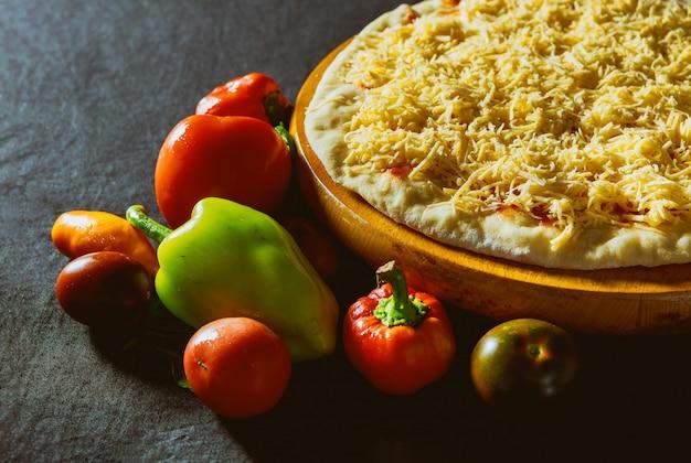 Closeup boulanger, fabrication de fromage sur une pizza à la cuisine