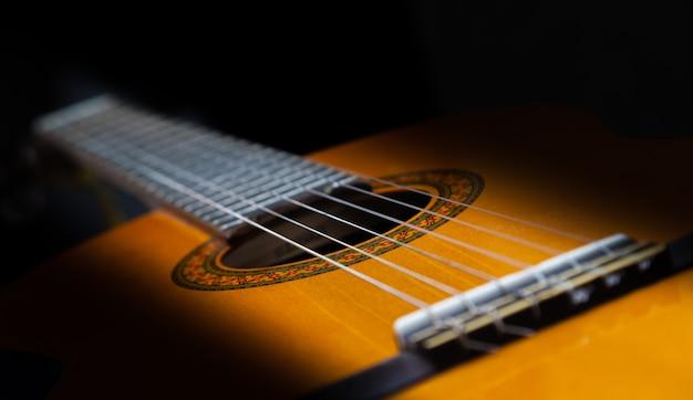 Closeup classique en bois de guitare jaune avec des cordes en nylon.