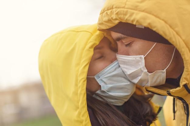 Closeup couple de baiser dans un masque médical, l'amour en temps de quarantaine